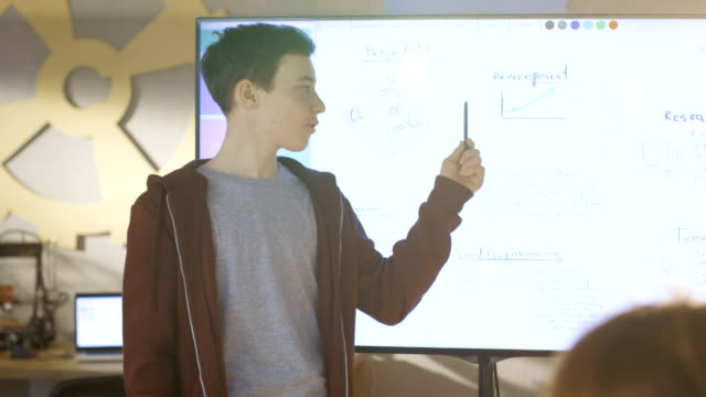 vídeos de stock, filmes e b-roll de menino mostra para a classe sua apresentação no quadro interactivo para seu projeto de escola próxima aula de ciências. - discurso