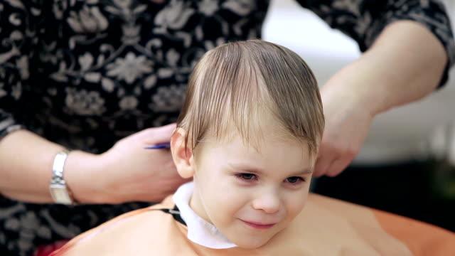 ragazzo canta mentre il barbiere taglio capelli - bassino video stock e b–roll