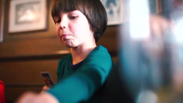 vídeos de stock, filmes e b-roll de um menino senta-se em uma tabela põr cartões sobre uma tabela em um jogo de placa - game