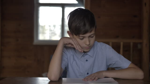 boy sits at the table and reads a book, village school