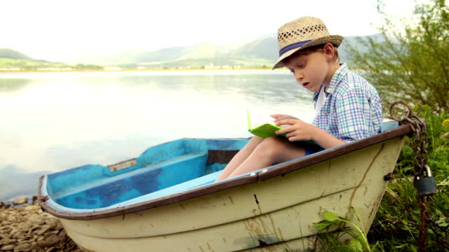 A boy sits in the moored at the bank boat reading a book video