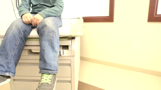 Boy Sits Nervously on Doctor Exam Table video