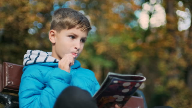 Boy Sits On Bench In A Park.