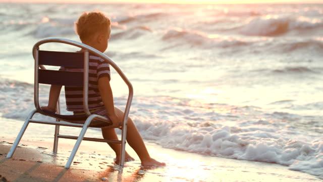 ragazzo seduto da solo su una sedia da mare - solo un bambino maschio video stock e b–roll
