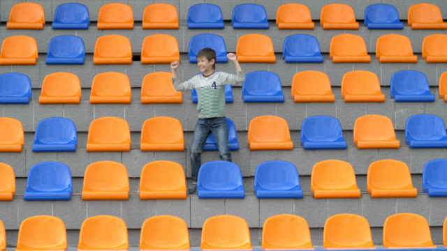 boy sitting at the stadium and glad his team scored a goal. happy boy watching match at stadium, boy shows emotion, the boy sits alone in the stadium hockey, ice hockey, soccer, basketball, volleyball video