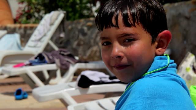 ragazzo seduto in piscina avvolti in un telo da mare - brent video stock e b–roll