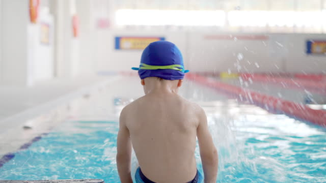 boy sitting by the swimming pool - solo un bambino maschio video stock e b–roll