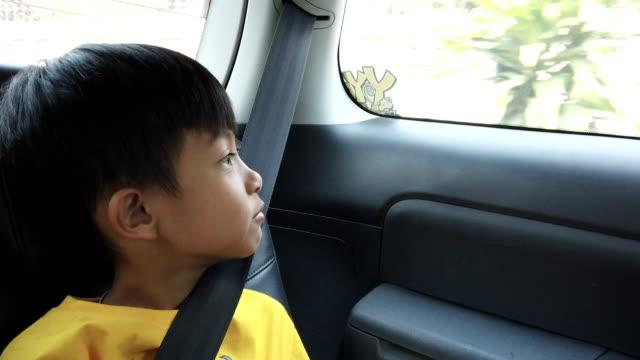 a boy sitting in car with safety belt - pojazd lądowy filmów i materiałów b-roll