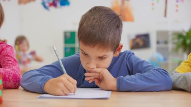 ds boy seduto nella luminosa classe e scrivendo nel suo taccuino - 8 9 anni video stock e b–roll