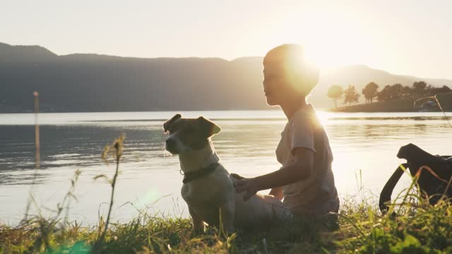 Boy sitting on a lake shore with his dog Jack Russell Terrier against the background of an orange sunset slow motion slide, rays of sun and shows off into horizon. Lens flare
