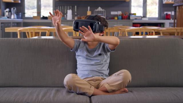 Boy Sitting On Sofa Wearing Virtual Reality Headset video