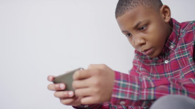Boy sitting on staircase using mobile phone