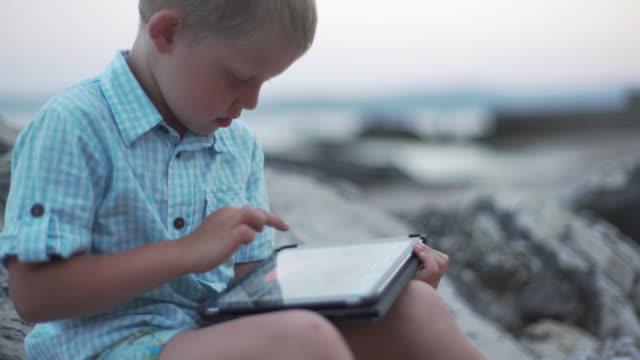 Boy sitting on the rocky shore.
