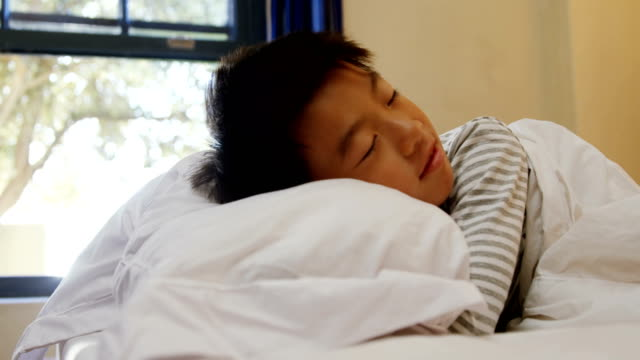 Boy sleeping on the bed in bed room 4k video
