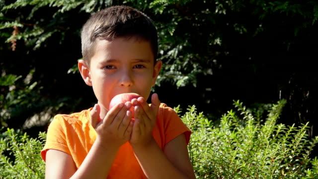 boy smells the aroma of peach - pesche bambino video stock e b–roll