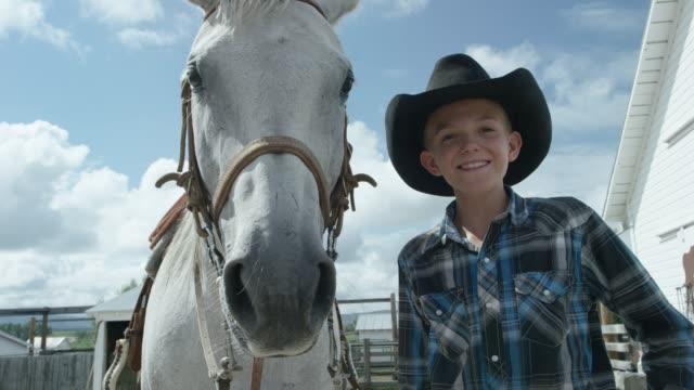 少年の笑顔、馬に見えます - ロデオ点の映像素材/bロール