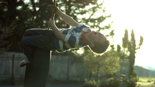 junge spinning auf reifen schwingen, zeitlupe - kind schaukel stock-videos und b-roll-filmmaterial