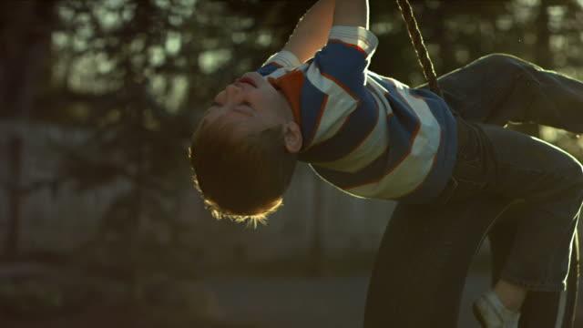 Boy spinning on tire swing video