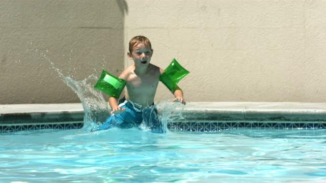 ragazzo un tuffo in piscina, rallentatore - solo un bambino maschio video stock e b–roll