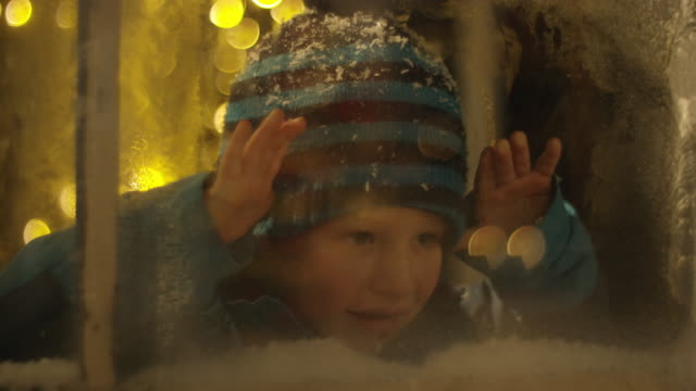 Boy spying on Santa Claus behind snowy window video