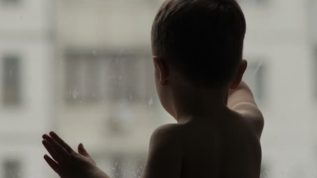 Boy Standing Near The Window With Hands On Window Glass Kid Waiting For  Parents Waiting Concept Stock Video - Download Video Clip Now - iStock