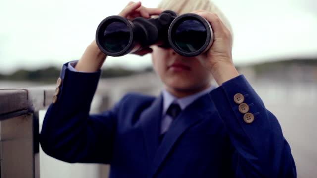 Boy (8-9) standing outdoors using binoculars, lake in background video