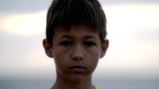 boy stands alone looking into the camera - fuggitivo video stock e b–roll