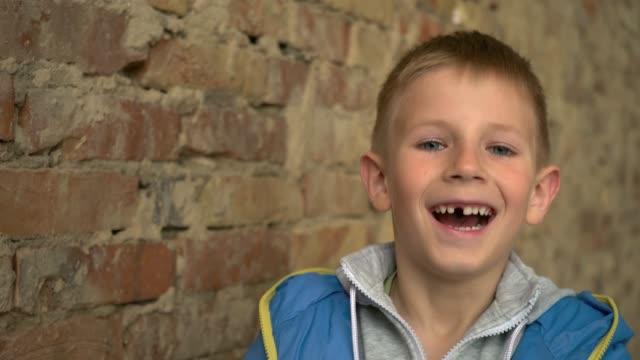 vídeos de stock, filmes e b-roll de o menino está perto da parede de tijolo. retrato de uma criança de seis anos de idade - fine dining
