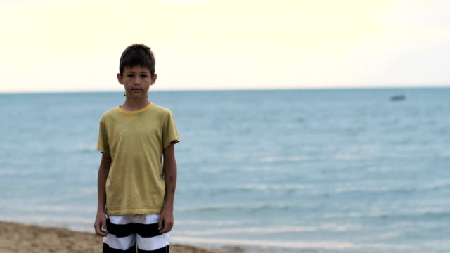boy stands on the beach near the sea and looks at the camera - fuggitivo video stock e b–roll