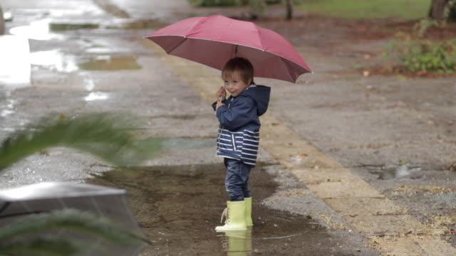 vídeos de stock e filmes b-roll de a boy stands with an umbrella and rubber boots in a puddle in the rain. - guarda chuva