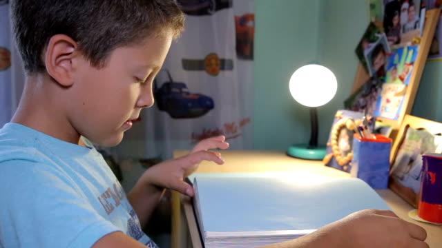boy starts reading encyclopedia - solo bambini maschi video stock e b–roll