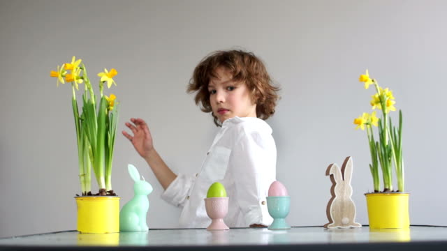 Boy steals an Easter egg, childish pranks. Curly cute schoolboy near the table with Easter decor. Easter traditions