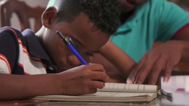 chłopiec studiuje edukację z ojcem pomaga syn robi pracę domową w szkole - praca domowa filmów i materiałów b-roll