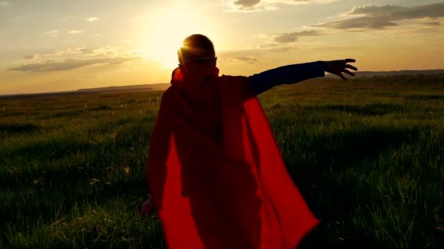 junge superhelden im einem feld während dem sonnenuntergang - held stock-videos und b-roll-filmmaterial