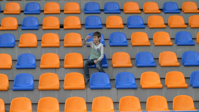 boy swears football team because she missed a goal, team loses, fan boy upset, boy looks at the stadium football match, boy watching the game of his team at the stadium, hockey, basketball, volleyball video