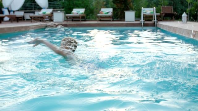 Boy swimming in swimming pool video