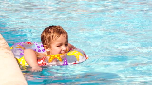boy swimming with inflatable ring - inflatable ring bildbanksvideor och videomaterial från bakom kulisserna