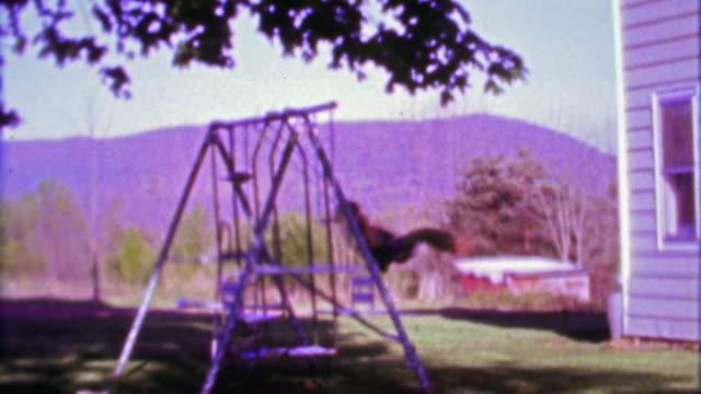 1968: Boy swing set in country rural mountainous setting. video