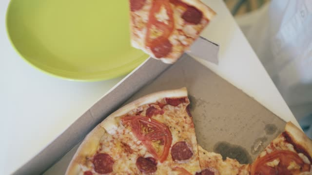 boy takes broken slice of pizza from box close upper view