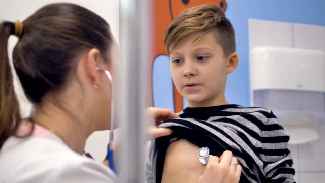 少年は医師の健康診断の時に深い呼吸します。 - 聴診器点の映像素材/bロール
