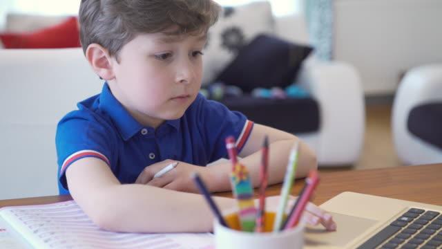 stockvideo's en b-roll-footage met jongen die online cursussen in woonkamer neemt - ver
