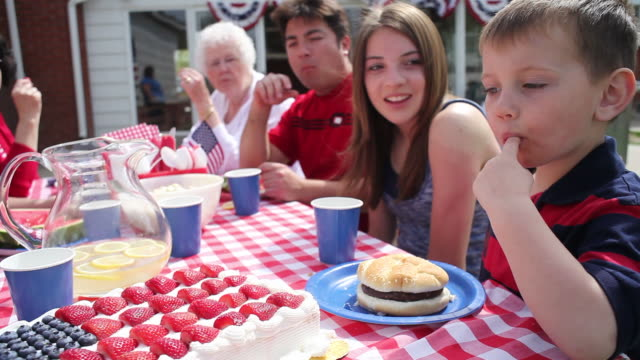 Boy tastes cake and smiles  family 4th of july stock videos & royalty-free footage