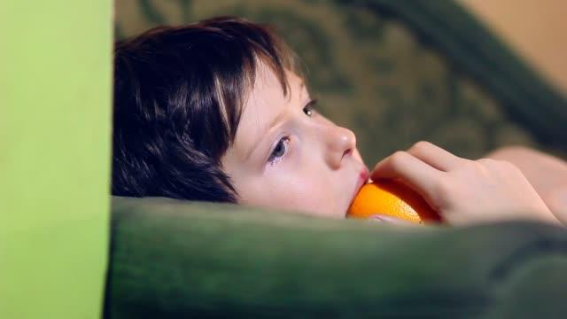 boy teenage is eating an orange and peel video