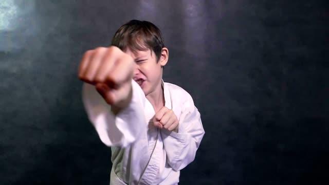 10 代の少年空手の着物ファイト手を振る・フィストスローモーション ビデオ