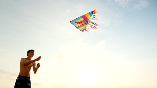 Boy teenager playing with a kite. Against the background of blue sky, view from below video