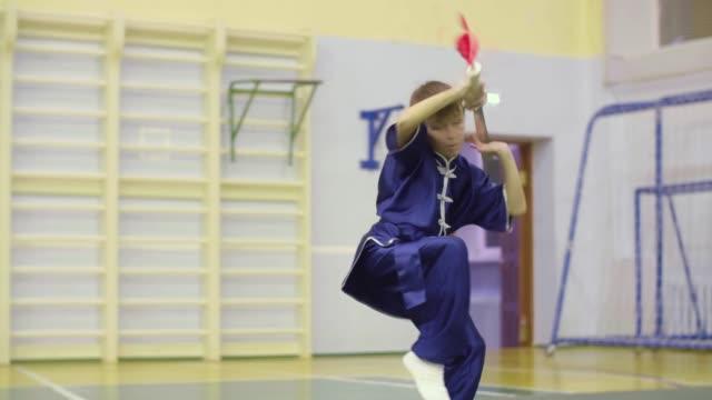 Boy teenager showing wushu exercises changquan while martial arts training