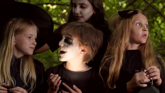 boy telling spooky stories to girls on halloween - four seasons filmów i materiałów b-roll