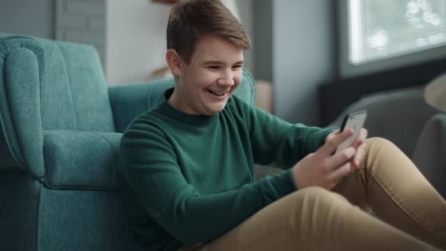 スマートフォンでの少年のテキストメッセージ - 男の子点の映像素材/bロール
