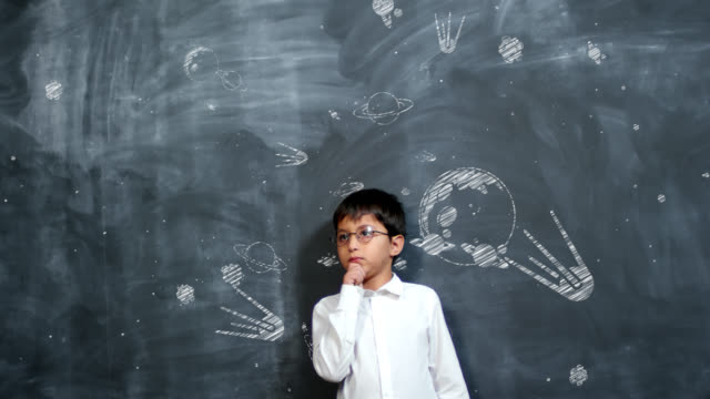 Boy Thinking at Blackboard with Animated Planets Genius little schoolboy in white shirt and eyeglasses standing against blackboard with animated chalk drawings of planets and shuttles flying in space, rubbing his chin and thinking genius stock videos & royalty-free footage
