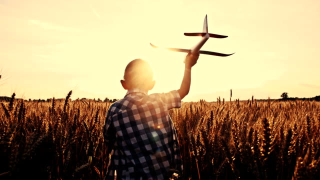 SLO MO Boy throwing airplane toy in wheat field
